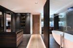 Luxe inloopkast met verhoging en badkamer met schuifdeuren
